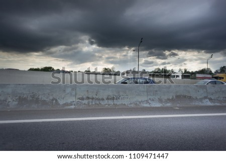 Urban Elevated Roads with concrete blocks on both sides. Black clouds on the sky. Storm is coming #1109471447