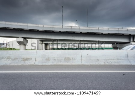 Urban Elevated Roads with concrete blocks on both sides. Black clouds on the sky. Storm is coming #1109471459