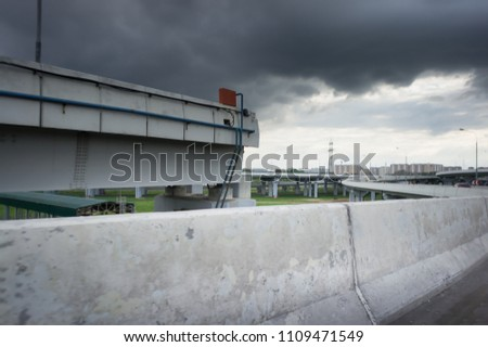 Urban Elevated Roads with concrete blocks on both sides. Black clouds on the sky. Storm is coming #1109471549