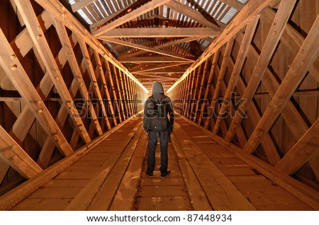 Urban explorer in an unused covered bridge #87448934