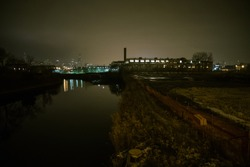 Urban fog river scenery with the Chicago skyline, a vintage factory building and an empty lot at night.