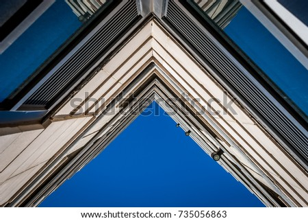 Urban Geometry, looking up to building. Modern architecture with concrete and glass blue sky background.  Abstract architectural design. Inspirational. Artistic image and point of view.