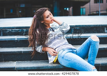 urban girl portrait on stairs in blue jeans and shirt