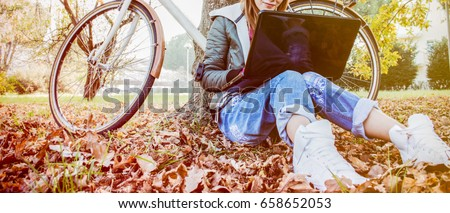 Urban girl with laptop in park. slim hipster woman in jeans using notebook with bicycle sitting on the grass. freelancer using communication technology remote work and eco-friendly  lifestyle. #658652053