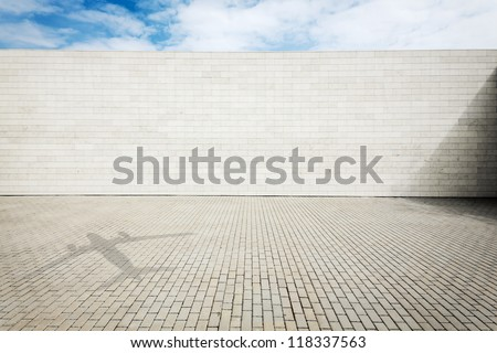 Urban grungy street wall with a shadow on the ground  of a plane flying by, may be used as background or texture