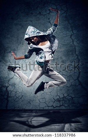 urban hip hop dancer with grunge concrete wall background texture jumping and dancing with hoodie - stock photo