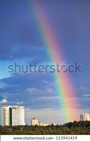 urban house under rainbow in dark blue sky