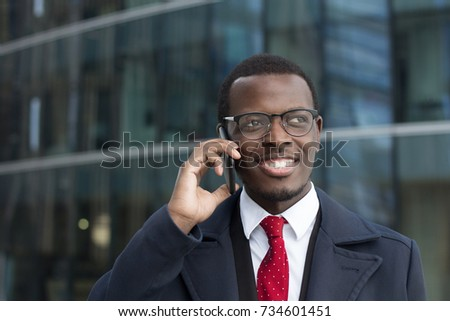 Urban image of handsome African entrepreneur spending break outside high city building looking aside to street while having pleasant conversation via cellphone about positive dynamics in business #734601451