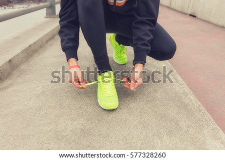 Urban jogger tying running shoes on the sidewalk.