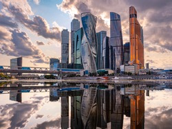 Urban landscape of steel color. Skyscrapers of Moscow are reflected in the water. Moskva-city. Tall buildings and gray clouds. Reflection. Panorama of modern Moscow.