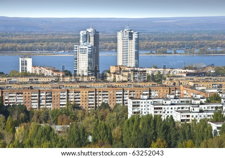 Urban landscape. Typical residential area on the riverbank. The view from the heights in the background high-rise apartment building. Russia. - stock photo