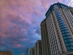 Urban landscape with multi-storey modern skyscraper against cloudy blue and pink sky. Business center cityscape. Office building architecture..High rise residential. Real estate property.