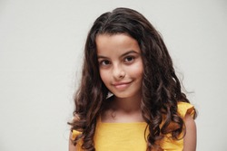 urban lifestyle portrait of a confident and gorgeous mixed race child face, multiethnic tween preteen teen girl with beautiful curly hair wearing yellow summer dress, smiling at camera, youth day
