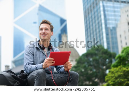 Urban man using tablet computer sitting in Hong Kong outside using app on 4g wireless device wearing headphones. Casual young urban professional male in his late 20s. Hong Kong Central. #242385751