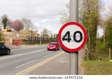 Urban 40 miles per hour speed limit sign used in the United Kingdom with defocussed traffic in the background #619472156