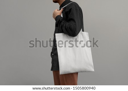 Urban mockup of tote bag. Men holding white cotton tote bag on a wall background. Template can be used for you design