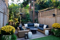 Urban, neutral, outdoor living space exterior photo. Outdoor living room with couch, comfy couch cushions, throw pillows, love seat, chairs and coffee table. Backyard lush with greenery and plants.