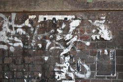 Urban old shabby weathered brick wall with graffiti tag scribbles and torn street posters