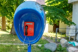 Urban payphone in the open air against the background of a Park close-up