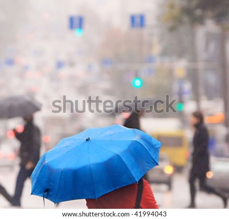 urban people cross the street in the rain