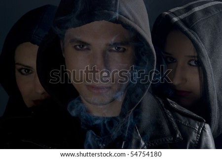 Urban people street in black hoods standing in darkness  with smoke around them and looking you.man in front and two women behind him