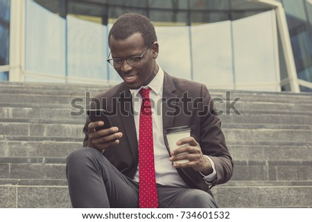 Urban photo of young handsome African American business guy spending leisure time on stairs in street drinking takeaway coffee and checking messages or communicating via smartphone with smile #734601532