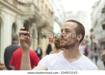 Urban photographer with mobila phone make photo on street