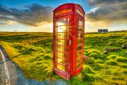 Urban red telephone box in the middle of a green countryside. Concept for synergy between modern and rural area. Red and green complementary colors join together in a scottish land, United Kingdom.