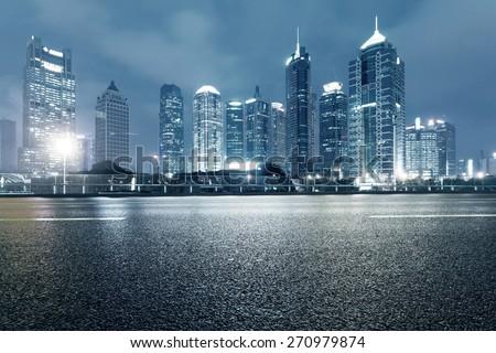 urban road,illuminated skyline background