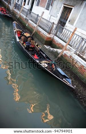 Urban scene in Venice, Italy. Empty gondola near dwelling house on a canal