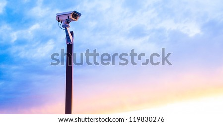 Urban security video camera outdoors at sunset