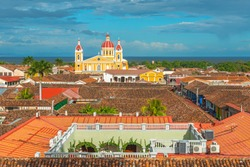 Urban skyline of Granada city at sunset with its spanish colonial architecture, colorful cathedral and beautiful rooftops with the Nicaragua Lake in the background, Nicaragua, Central America.