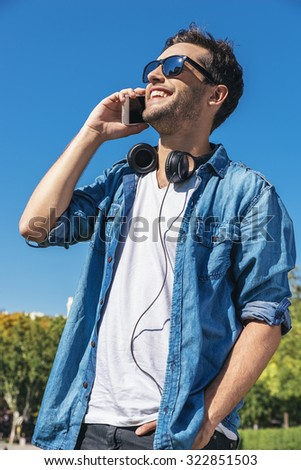 Urban smart casual handsome young man talking on smartphone. Happy male adult speaking on mobile phone. stock photo