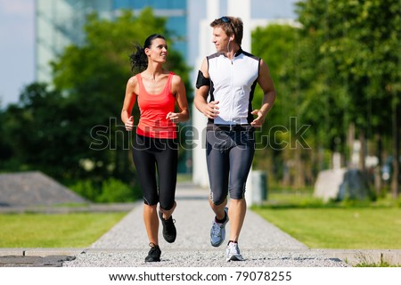 Urban sports couple jogging for fitness in the city on a beautiful summer day