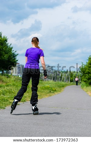 Urban sports - woman skating with Roller blades for better fitness in the city park on a cloudy summer day