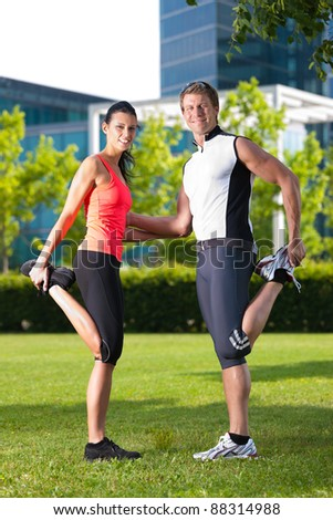 Urban sports - young couple is doing warming up before running in the city on a beautiful summer day