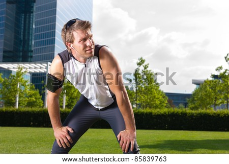 Urban sports - young man is doing warming up before running in the city on a beautiful summer day