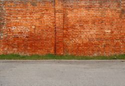 Urban street background. Old brick wall, a line of grass and an asphalt road