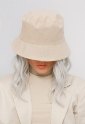 Urban street style Blonde. Details of everyday look. Casual beige aesthetic outfit and accessories. Bucket hat. Trendy Minimalist fashion