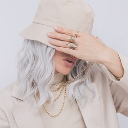 Urban street style Blonde. Details of everyday look. Casual beige outfit and accessories. Bucket hat and rings. Trendy Minimalist fashion