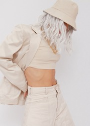 Urban street style Model in white studio. Details of everyday look. Casual beige outfit and accessories. Bucket hat. Trendy Minimalist fashion