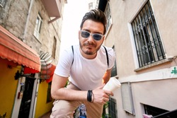 Urban style. Fashion portrait of a stylish young man with sunglasses posing on a street holding a coffee cup by the yellow wall. Male fashion. Colorfull background.