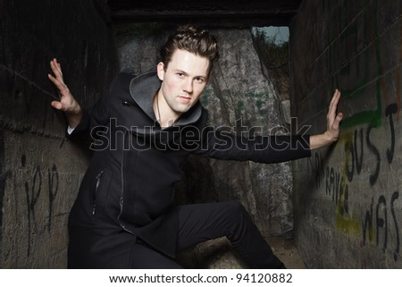 Urban style handsome young man with fifties hairstyle dressed in black