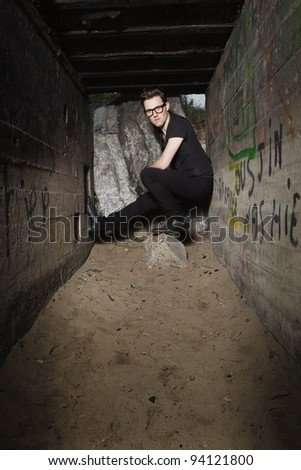 Urban style handsome young man with fifties hairstyle dressed in black wearing glasses