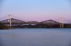 Urban sunset landscape over the historic infrastructure of The Quebec Bridge in Quebec city, Canada