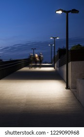 Stock photo of urban surroundings at late evening, with street lights and three unrecognizable persons walking upwards concrete pavement. Movement blurred, back view.