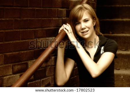 Urban Teen:  A teenage girl sits on a stairway near a brick building in a high contrast sepia image with a slight grain for an edgy, grungy look.