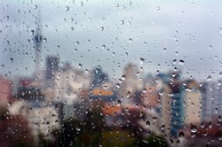 Urban view of rain drops falls on a window during a stormy day overlooking Auckland financial district  New Zealand skyline in the background.