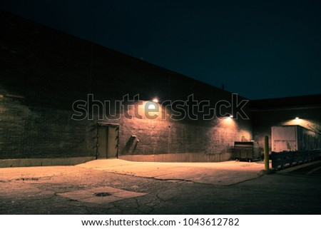 Urban warehouse building and loading dock with a semi trailer at night