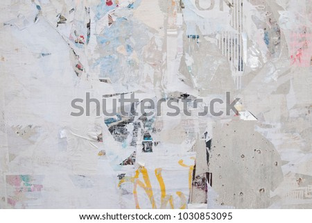 urban weathered exposed concrete wall with ripped torn street poster